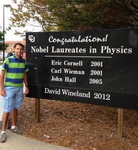 Carlos Hernández-García junto a una placa distintiva con los premios Nobel en Física logrados en la Universidad de Colorado.